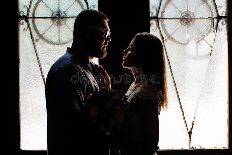 Portrait of a romantic couple in a backlight from a window or door, silhouette of a couple in a doorway with a backlight, couple o stock image