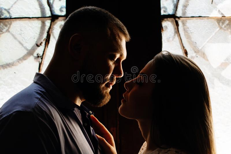 Portrait of a romantic couple in a backlight from a window or door, silhouette of a couple in a doorway with a backlight, couple o royalty free stock photography