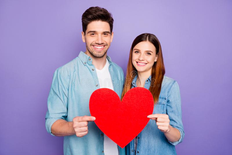 Portrait of romantic two married people couple hold paper card red heart gift for valentine day enjoy date wear stylish royalty free stock photography