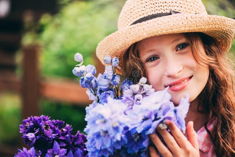 Portrait romantique du bouquet heureux de cueillette de fille d'enfant de belles fleurs bleues de delphinium image stock