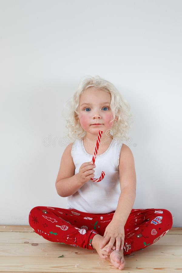 Portrait of rouge blonde adorable girl wears casual clothes or pyjamas, sits crossed legs, holds red and white caramel royalty free stock photography