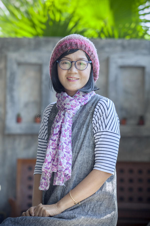 portrait of 40s years asian woman wearing wool hood and silk scarf toothy smiling with happiness emotion royalty free stock photo