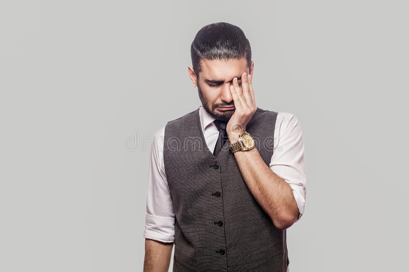 Portrait of sad alone depressed handsome bearded brunette man in white shirt and waistcoat standing, holding head down, touching. Eyes and crying. indoor studio royalty free stock photo
