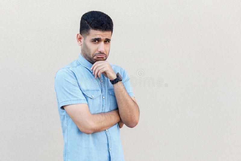 Portrait of sad alone handsome young bearded businessman in blue shirt standing and looking at camera with sadness or worried face royalty free stock photo