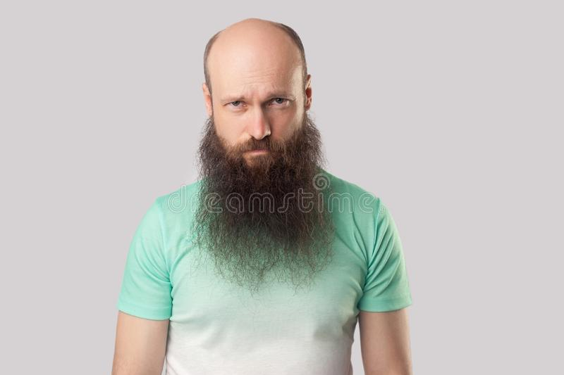 Portrait of sad alone middle aged bald man with long beard in light green t-shirt standing, frowning and looking at camera with. Upset face. indoor studio shot stock photo