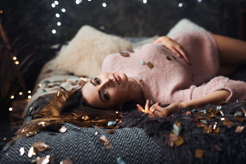 Portrait of sad attractive young woman with tinsel confetti and garland lights celebrating alonein dark room. New year`s stock photography