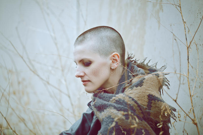 Portrait of sad beautiful Caucasian white young bald girl woman with shaved hair head in leather jacket and scarf royalty free stock image