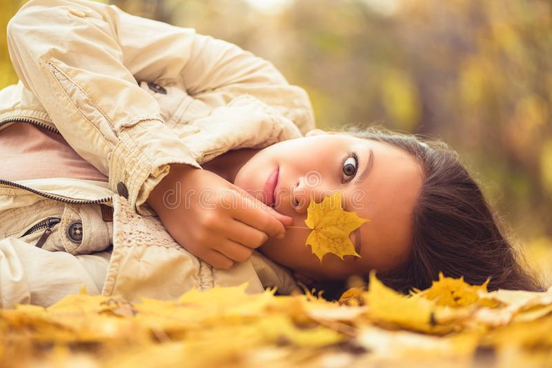 Portrait of sad beautiful young woman lying on the ground of an autumn forest with colorful maple leaves. Concept. royalty free stock images