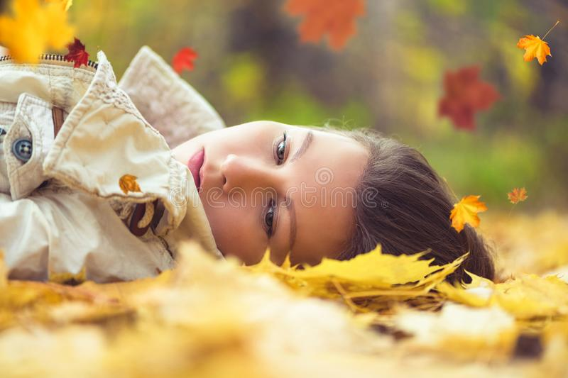 Portrait of sad beautiful young woman lying on the ground of an autumn forest with colorful maple leaves. Concept. stock photography