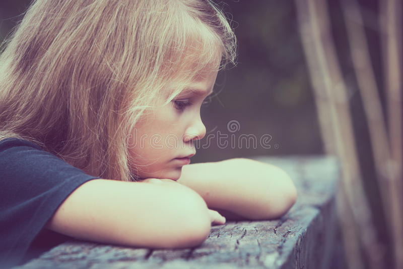 Portrait of sad blond little girl sitting on the bridge stock photo