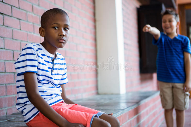 Portrait of sad boy in school corridor. Portrait of sad boy with classmate laughing on him in background at school corridor royalty free stock image