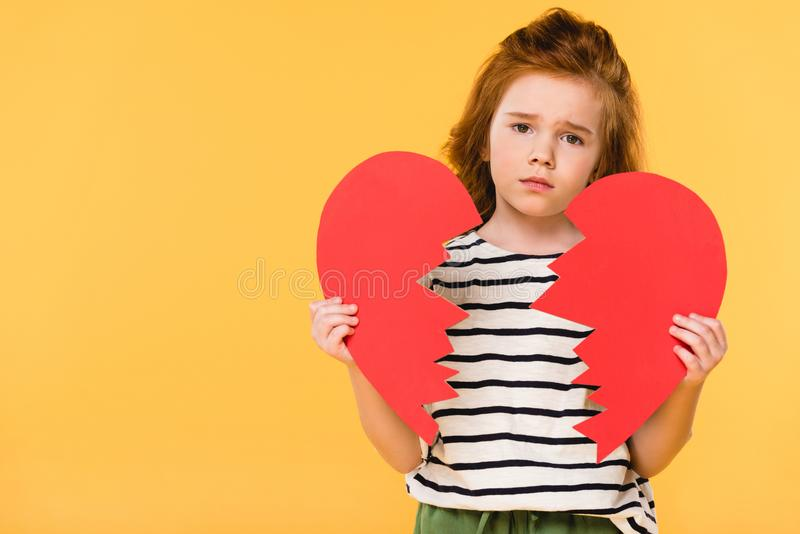 Portrait of sad child with broken red paper heart. Isolated on yellow, st valentines day concept royalty free stock image