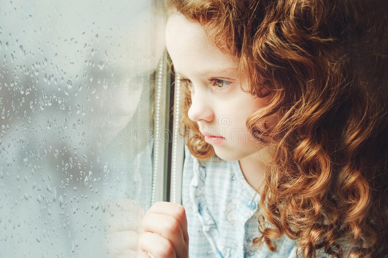 Portrait of a sad child looking out the window. Toning photo. Sad child looking out the window. Toning photo