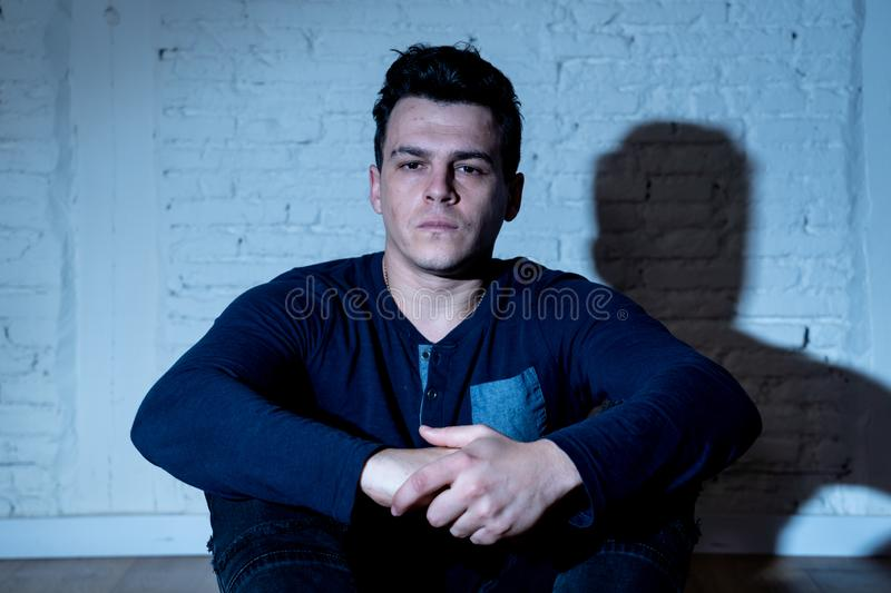 Desperate lonely unhappy caucasian man suffering from depression sitting alone on floor at home. Portrait of sad depressed young man crying devastated feeling royalty free stock images
