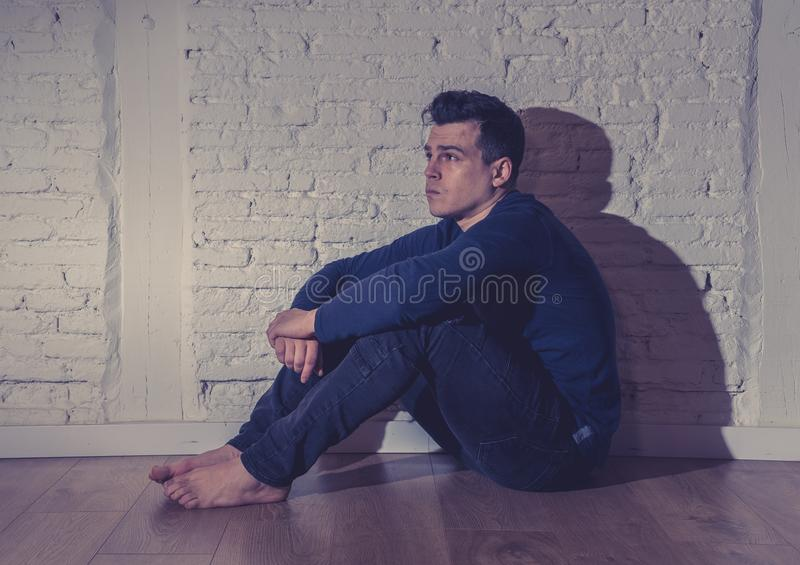 Desperate lonely unhappy caucasian man suffering from depression sitting alone on floor at home. Portrait of sad depressed young man crying devastated feeling stock image