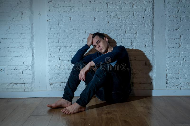 Desperate lonely unhappy caucasian man suffering from depression sitting alone on floor at home. Portrait of sad depressed young man crying devastated feeling stock photo