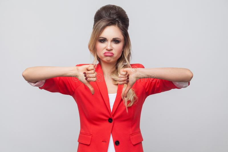 Portrait of sad dissatisfied beautiful business lady with hairstyle and makeup in red fancy blazer, standing with thubms down and. Looking at camera. indoor stock photos