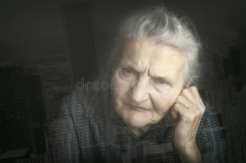 Portrait of a sad elderly woman, double exposure. Dreaming the p stock photography