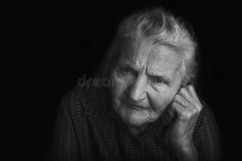 Portrait of a sad elderly woman. Dreaming the past. royalty free stock photography