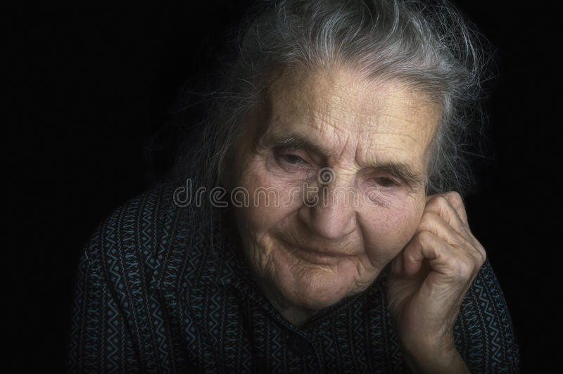 Portrait of a sad elderly woman. Dreaming the past. stock photography