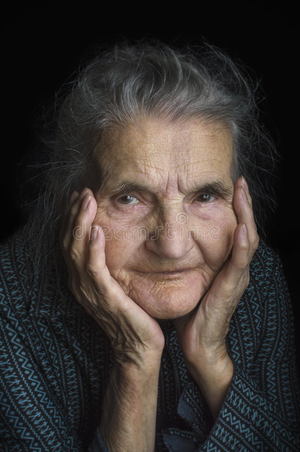 Portrait of a sad elderly woman. Dreaming the past. stock photo