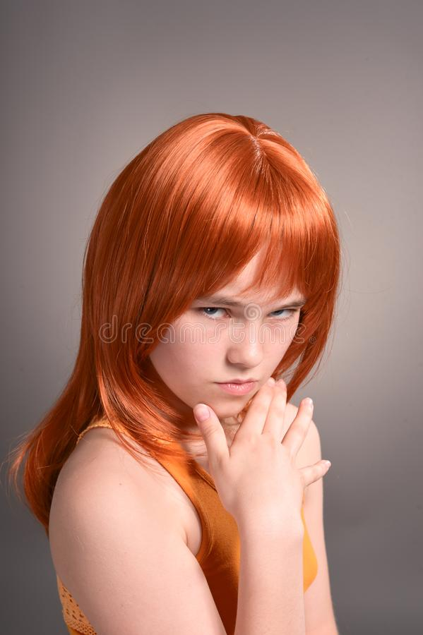 Portrait of sad girl with red hair posing in studio stock photo