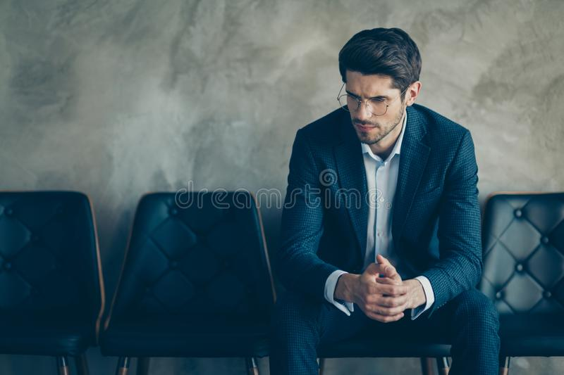 Portrait of sad guy feel nervous wait for meeting with new boss hr interview look pensive minded sit chair wear stylish. Portrait of sad guy feel nervous wait stock image