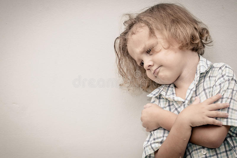 Portrait of sad little boy. Standing near the wall royalty free stock photo