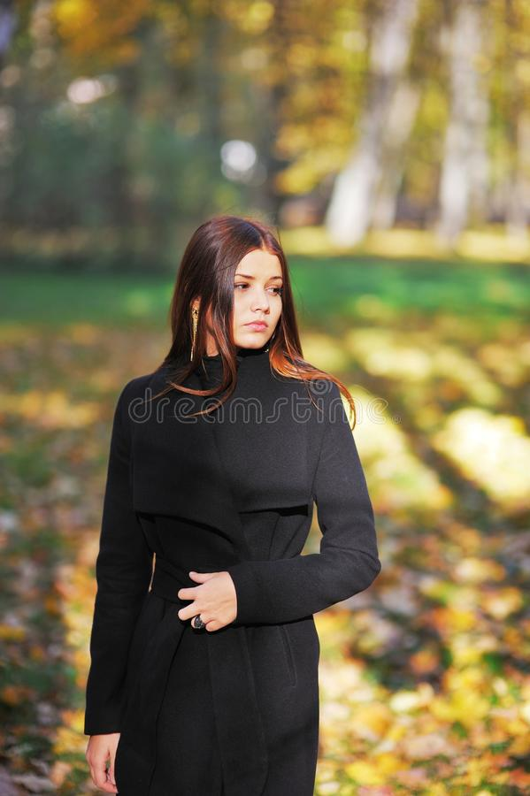 Portrait of a sad, long-haired girl in an elegant black cardigan on sunny day in autumn park. stock photo