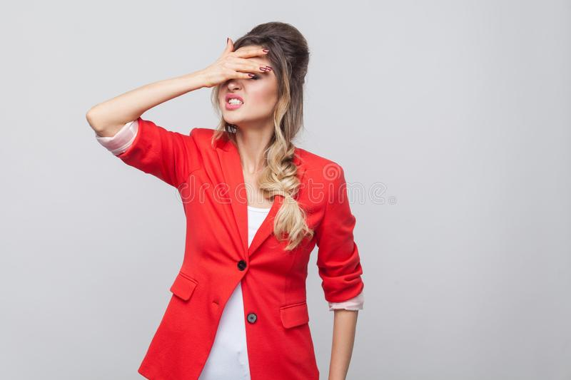 Portrait of sad lose beautiful business lady with hairstyle and makeup in red fancy blazer, standing holding hand on her forehead. Indoor studio shot, isolated royalty free stock photography