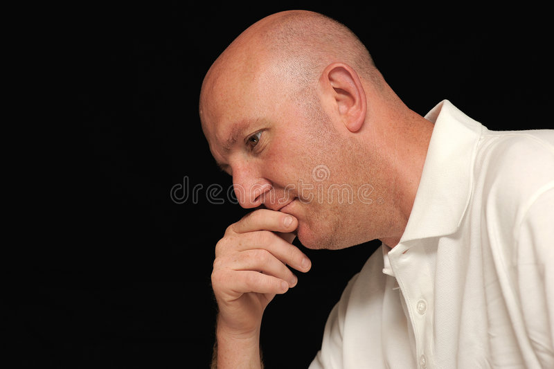 Portrait of sad man. Portrait of sad bald man with hand to his mouth, black background royalty free stock photos