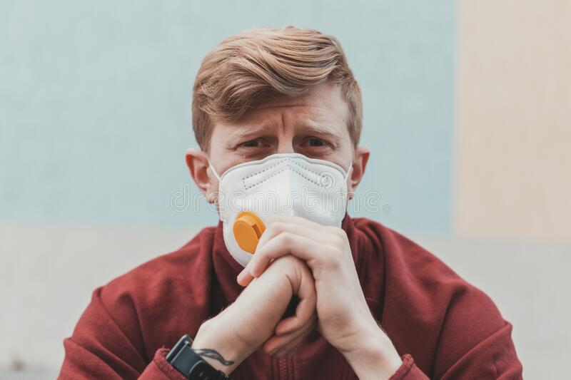Portrait of a sad man with a dramatic facial expression in a protective mask against the virus during quarantine.  stock photography