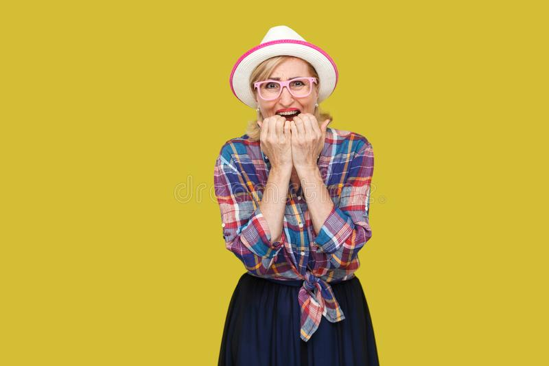 Portrait of sad nervous modern stylish mature woman in casual style with hat and eyeglasses standing, bitting nails and looking at. Camera and panic. indoor royalty free stock photo