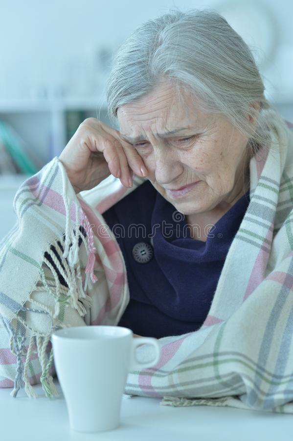 Portrait of a sad old woman crying at home. Portrait of a sad old woman crying royalty free stock images