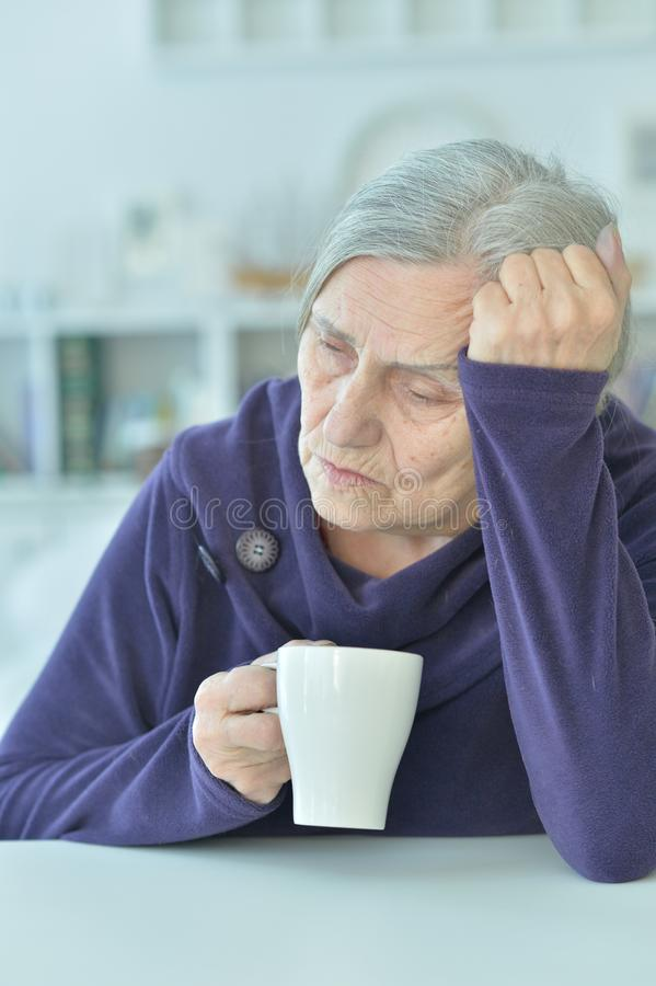 Portrait of a sad old woman drinking tea. At home royalty free stock photo