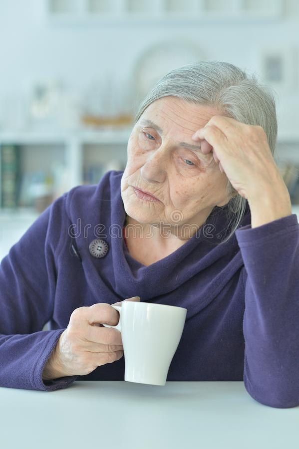 Portrait of a sad old woman drinking tea. At home royalty free stock photography