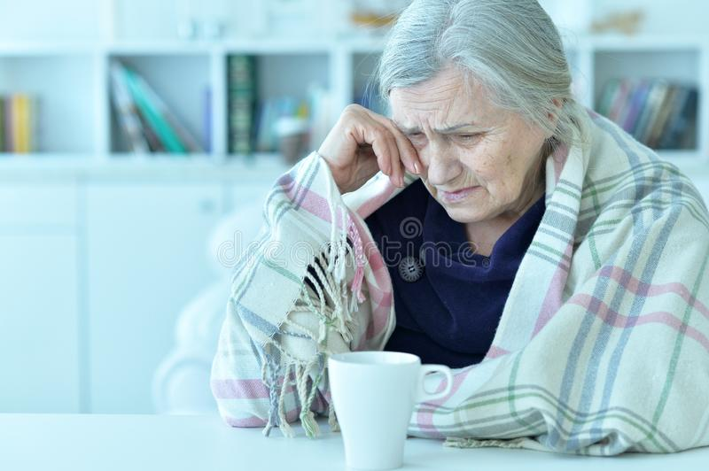 Portrait of a sad old woman drinking tea. At home stock photos
