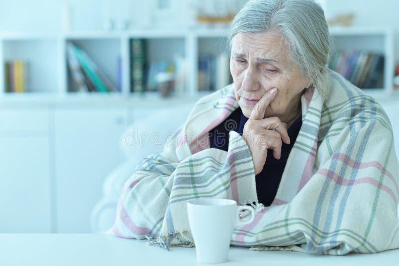 Sad old woman with headache drinking tea. Portrait of a sad old woman with headache drinking tea stock image