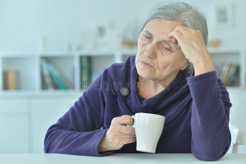 Sad old woman with headache  drinking tea. Portrait of a sad old woman with headache  drinking tea stock photo