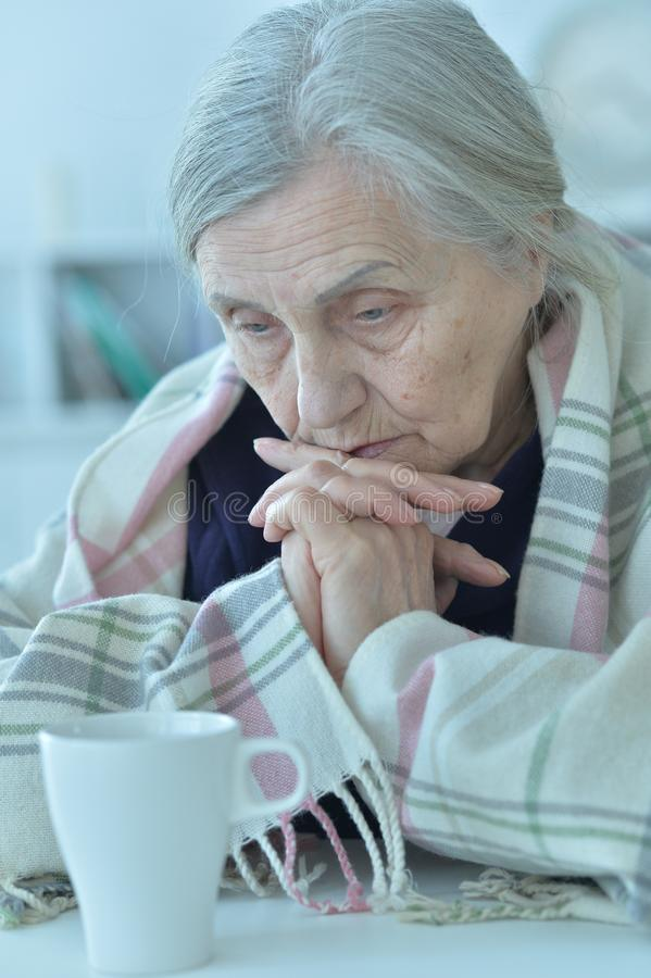 Portrait of a sad old woman at home. Portrait of a sad old woman wearing plaid royalty free stock image