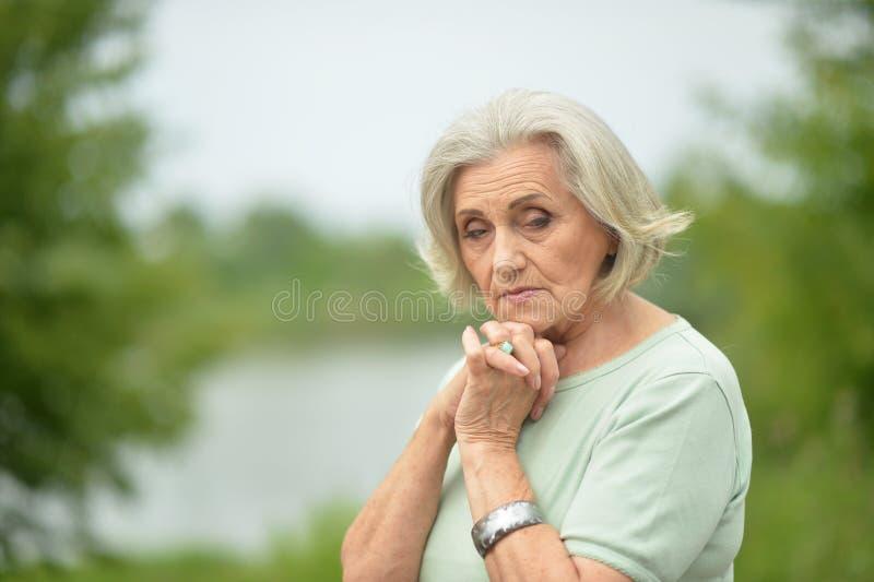 Portrait of sad senior beautiful woman in spring park. Sad senior beautiful woman posing in spring park stock photography