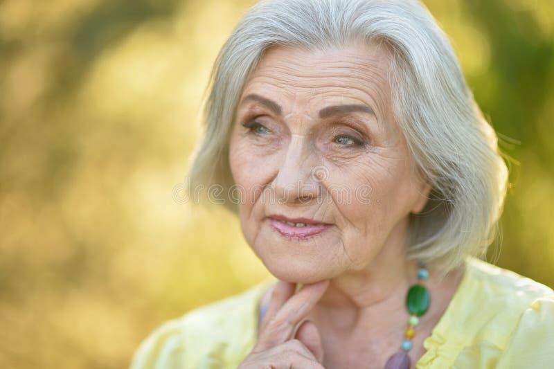 Portrait of sad senior beautiful woman in spring park. Sad senior beautiful woman posing in spring park stock photo