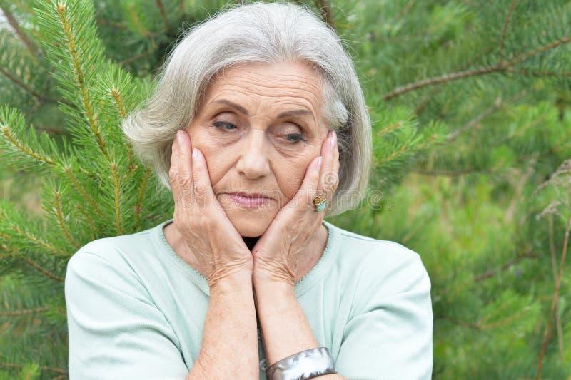 Portrait of sad senior beautiful woman in spring park. Sad senior beautiful woman posing in spring park stock photos
