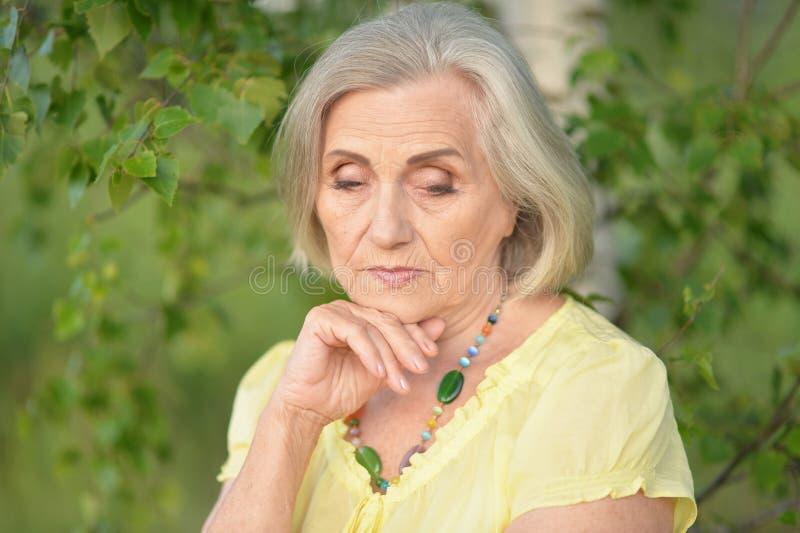 Portrait of sad senior beautiful woman in spring park. Sad senior beautiful woman posing in spring park stock image