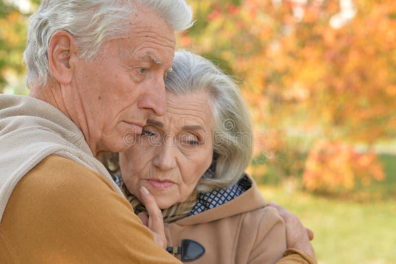 Portrait of sad senior couple in autumn park royalty free stock image