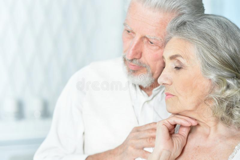 Portrait of sad senior couple posing at home stock images