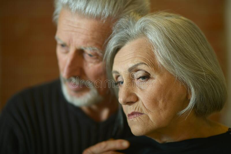 Portrait of sad senior couple posing at home stock photos