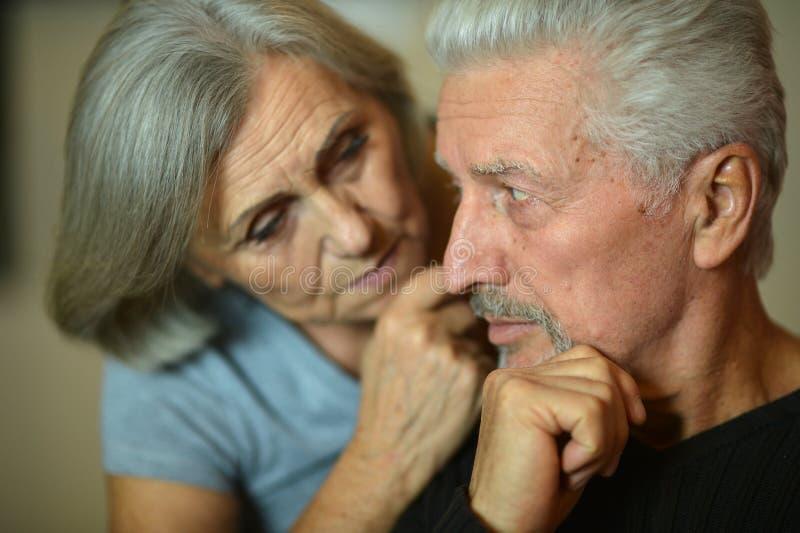 Portrait of sad senior couple posing at home royalty free stock photography