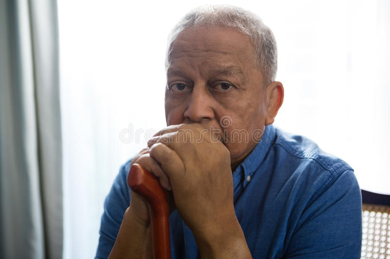Portrait of sad senior man holding walking cane while sitting on chair. In nursing home stock photography