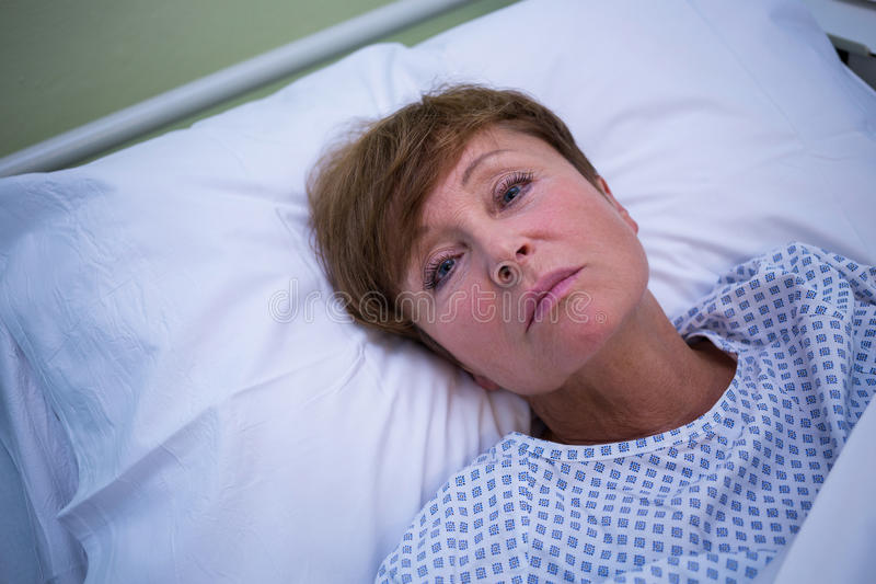 Portrait of sad senior patient lying on a bed royalty free stock images